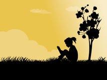 Das Mädchen, das auf einem Gras sitzt Lizenzfreies Stockfoto