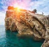 Das Mädchen, das auf einer felsigen Klippe nahe dem Meer im Sonnenlicht steigt Stockbild