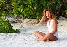 Das Mädchen, das auf Küste sitzt lizenzfreies stockfoto