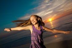 Das Mädchen, das auf schönen Strand springt und tanzt. Stockfoto
