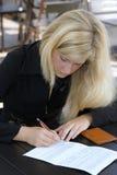 Das Mädchen, das den Vertrag unterzeichnet Lizenzfreie Stockfotografie