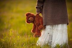 Das Mädchen, das in der Hand braunen Teddybären hält, betreffen Morgenfeld Lizenzfreie Stockfotos