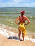 Das Mädchen, das an der Seeküste steht Stockfoto