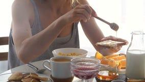 Das Mädchen, das in der weißen Küche sitzt und essen Pfannkuchen stock video