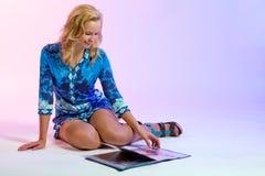 Das Mädchen, das durch eine Art und Weisezeitschrift schaut Lizenzfreies Stockfoto