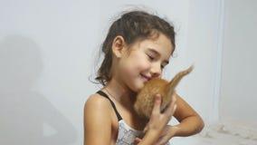 Das Mädchen, das ein kleines rotes Kätzchen streichelt, hält Katze stock footage