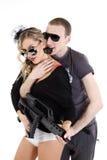 Das Mädchen, das eine Waffe mit Männer anhält, ist Stockfotografie