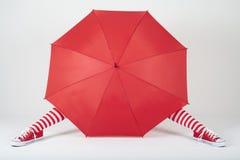 Das Mädchen, das hinter einem großen roten Regenschirm sich versteckt Stockfotos