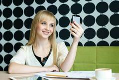 Das Mädchen, das im Café sitzt, hält einen Handy Lizenzfreie Stockfotografie