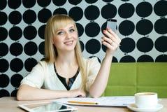 Das Mädchen, das im Café sitzt, hält einen Handy Stockfoto