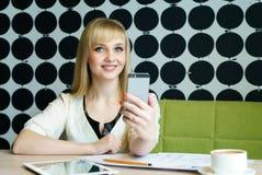 Das Mädchen, das im Café sitzt, hält einen Handy Stockbilder
