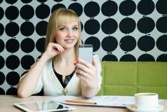 Das Mädchen, das im Café sitzt, hält einen Smartphone Lizenzfreie Stockfotografie