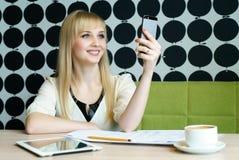 Das Mädchen, das im Café sitzt, hält einen Smartphone Lizenzfreies Stockfoto
