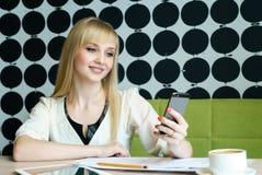 Das Mädchen, das im Café sitzt, hält einen Smartphone Stockfotografie