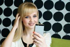 Das Mädchen, das im Café sitzt, hält einen Smartphone Stockfotos