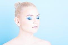 Das Mädchen, das mit Augen aufwirft, schloss und Make-up des blauen Auges Stockbild