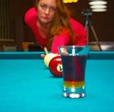 Das Mädchen, das Pool spielt, hat den Ball und wird im Glas reflektiert stockfoto
