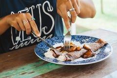 Das Mädchen, das süße Pfannkuchen isst, diente auf blauer Platte mit Creme Lizenzfreies Stockfoto