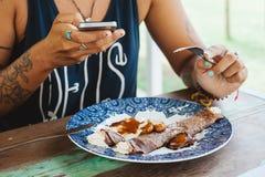 Das Mädchen, das süße Pfannkuchen isst, diente auf blauer Platte mit Creme Stockfotografie