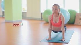 Das Mädchen, das tut, Übung für Dorn aufwärmend zurück, biegen sich und wölben sich, sie zurück zu Hause ausarbeitend oder Yogakl stock video footage
