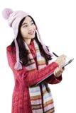 Das Mädchen, das warme Kleidung trägt und schreibt auf Klemmbrett Stockfotografie