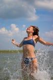 Das Mädchen, das in Wasser mit springt, spritzt Lizenzfreie Stockfotografie