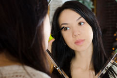 Das Mädchen, das Wimperntusche anwendet, bilden lizenzfreie stockfotos