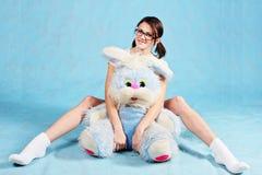Das Mädchen in den Gläsern mit einem weichen Spielzeugkaninchen Stockfotografie