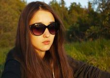 Das Mädchen in den Gläsern sitzt mitten in dem Wald und aalt sich in der Sonne stockfotos