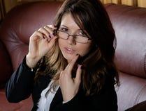 Das Mädchen in den Gläsern und im Anzug auf einem Sofa Stockfotos