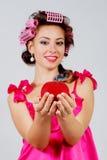 Das Mädchen in den Haarlockenwicklern mit einem roten Apfel in ihrer Hand Grauer Hintergrund Lizenzfreies Stockfoto