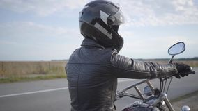 Das Mädchen, das den schwarzen Sturzhelm sitzt auf dem Motorrad schaut weg auf der Straße trägt Hobby, Reisen und aktiver Lebenss stock video footage