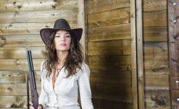 Das Mädchen der Cowboy mit einem Gewehr Stockbild