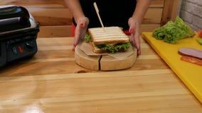 Das Mädchen in der Küche fügt einen hölzernen Stock in das gerade-zusammengebaute Sandwich ein Ein Weißbrotsandwich mit neuem grü stock footage