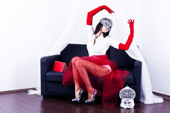 Das Mädchen in der Maske in den roten Handschuhen Stockbilder