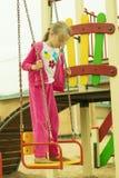 Das Mädchen in der roten Klage, die auf einem Schwingen steht Stockfoto