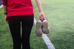 Das Mädchen in der Sportkleidung geht durch das Stadion und hält Turnschuhe in ihren Händen lizenzfreie stockfotos