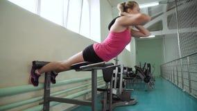 Das Mädchen in der Turnhalle führt eine Übung auf den Muskeln der Rückseite durch Hyperextension stock video footage