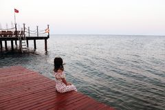 Das Mädchen, das durch das Meer saß und das Meer sah stockfotos