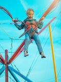 Das Mädchen, das durch rote Sicherheitsgurte gebunden wird, geht oben auf die Anziehungskraft Lizenzfreie Stockfotografie