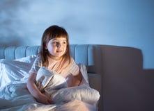 Das Mädchen, das durchdacht auf dem Bett in der Nacht sitzt Stockbild