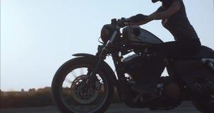 Das Mädchen, das ein Motorrad fährt, fährt entlang eine Landstraße an der Seitenansicht des Sonnenuntergangs stock footage
