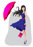 Das Mädchen in einem blauen Kleid mit einem Regenschirm Stockfotos