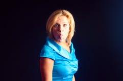 Das Mädchen in einem blauen Kleid setzt heraus die Zunge Stockfotos