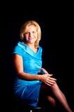 Das Mädchen in einem blauen Kleid sitzt auf einem Stuhl a Stockbilder
