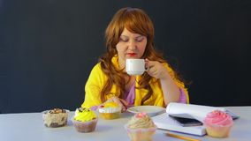 Das Mädchen in einem Café an den trinkenden Tee- und Kuchen der Tabelle essen stock footage