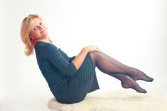 Das Mädchen in einem dunklen Kleid sitzt das Halten für Füße Stockfoto