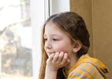 Das Mädchen an einem Fenster sitzt Stockfoto