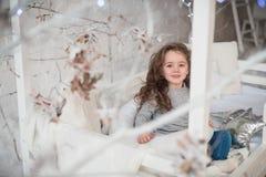Das Mädchen in einem grauen Pullover sitzt auf einem Bett der Kinder lizenzfreies stockbild