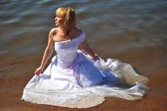 Das Mädchen in einem Hochzeitskleid im Wasser Stockbild